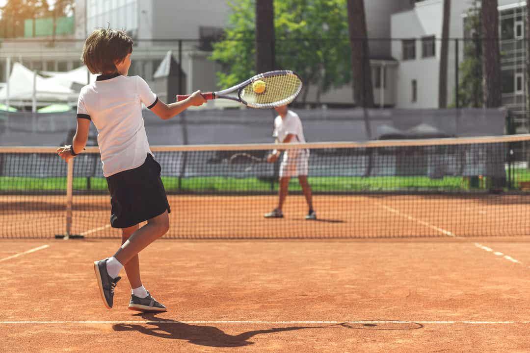 Et barn som spiller tennis med en voksen.