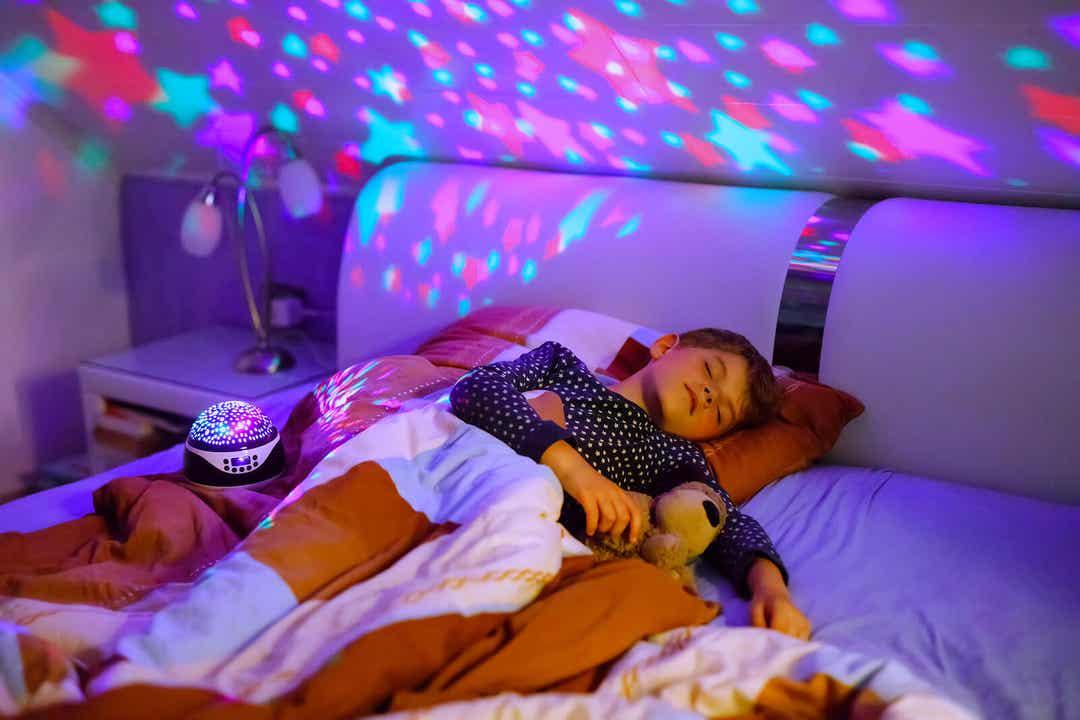 Een kind dat slaapt naast een sterrenprojector.