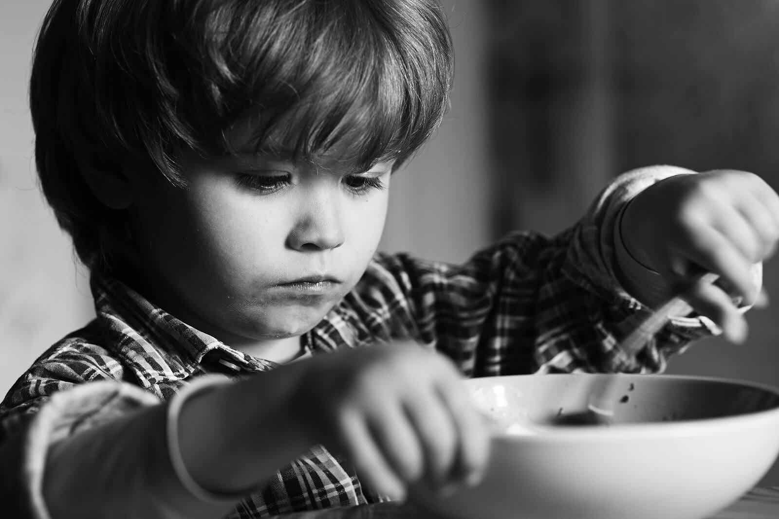 A black and white photo of a child eating a bowl of food with a serious face.
