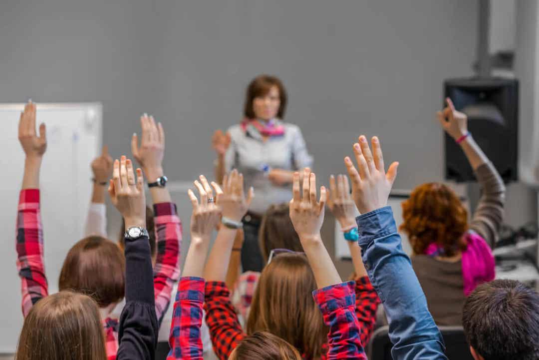 Ungdomsstudenter løfter ivrig hendene i timene.