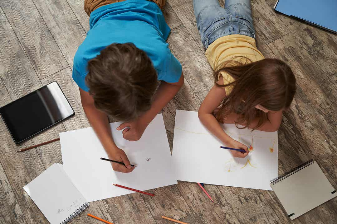 A boy and a girl lying on the floor drawing.