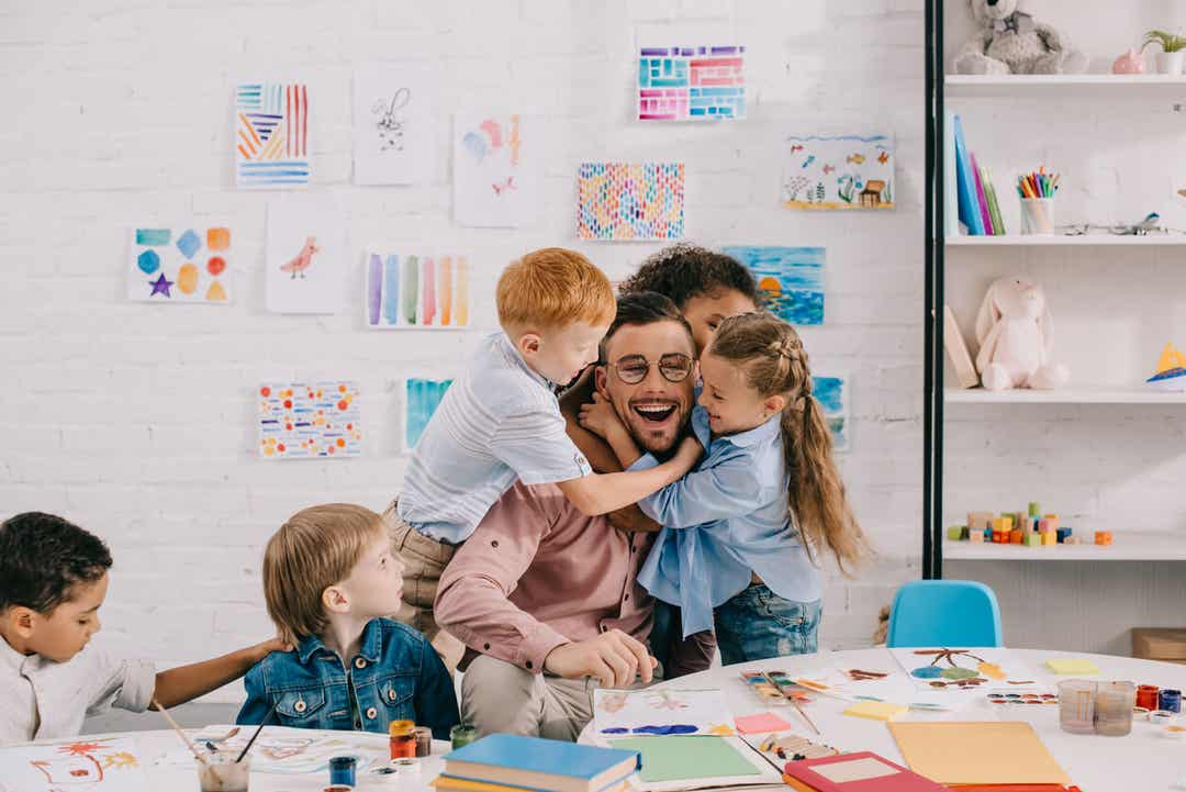 Elementary students hugging their teacher.