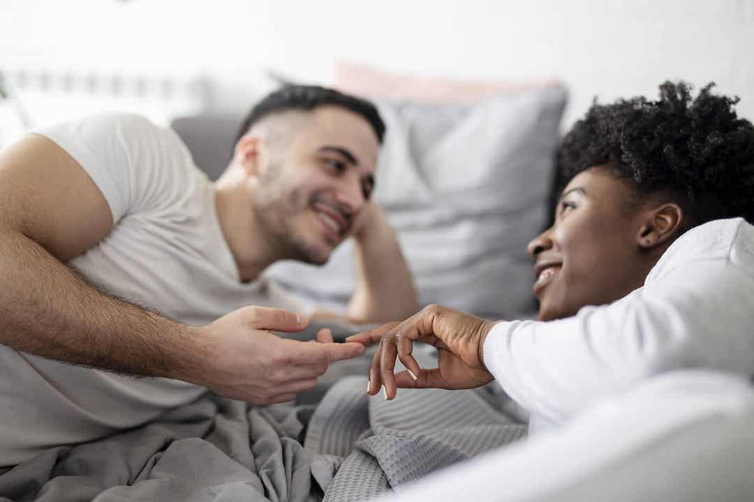 Para dotykająca opuszków palców i patrząca sobie w oczy w łóżku.