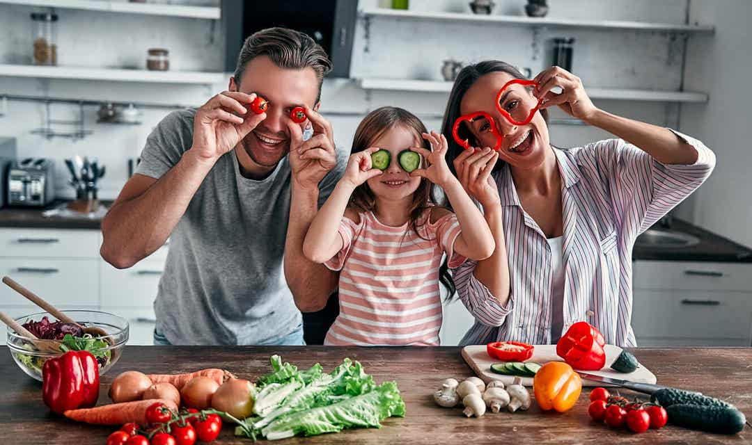A family playing with vegetables.
