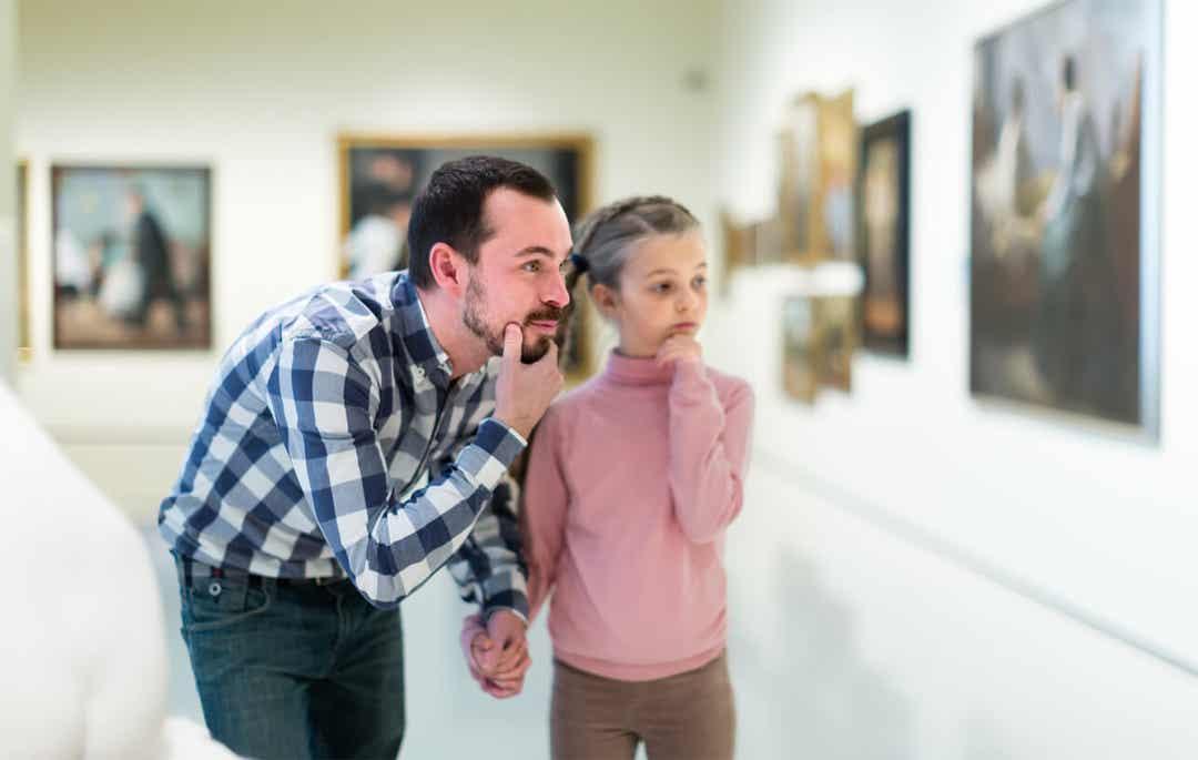 Ojciec z córką oglądają obraz w galerii.
