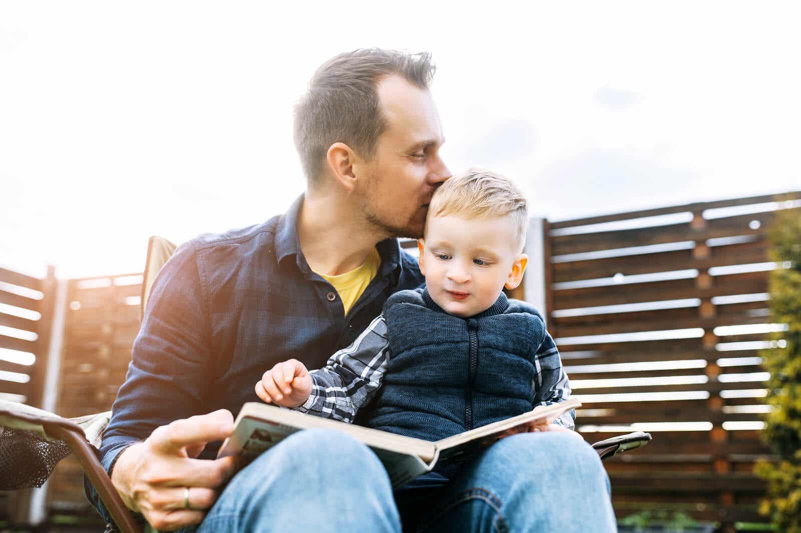 En far læser en bog udendørs med sin søn på skødet