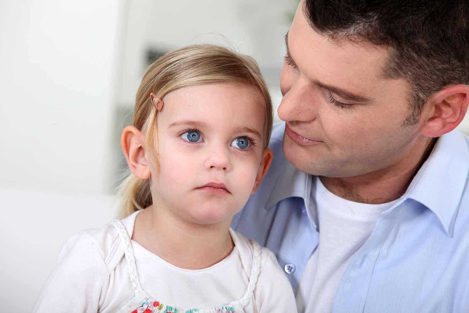 Een vader met zijn jonge dochter op schoot.
