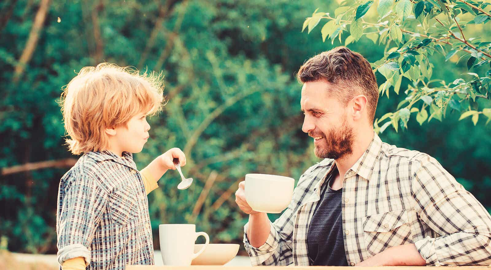 A father drinking having coffee with his son.