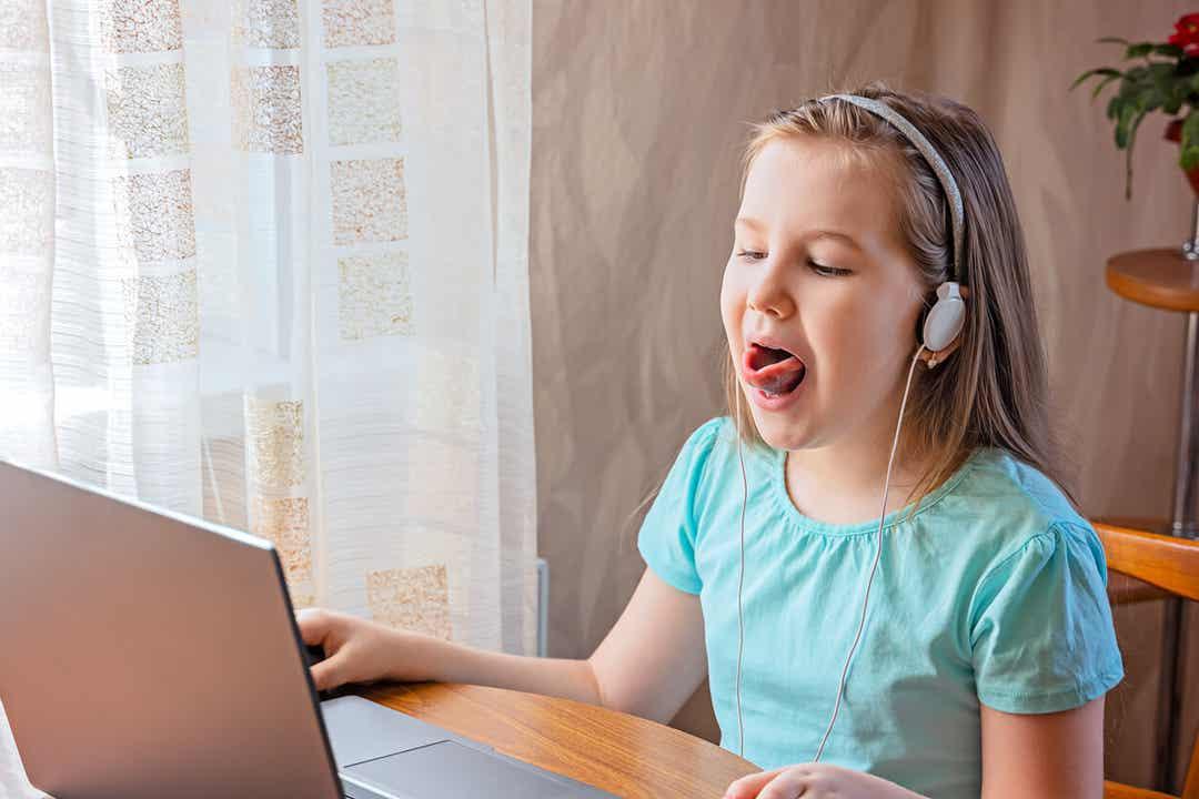 Een jong meisje doet tongoefeningen tijdens een online logopediesessie.