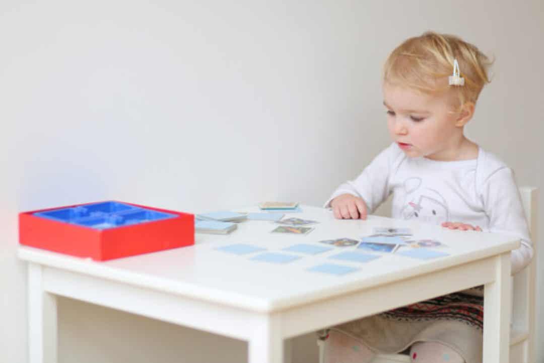 Maluch siedzący przy stole i bawiący się kartami pamięci.
