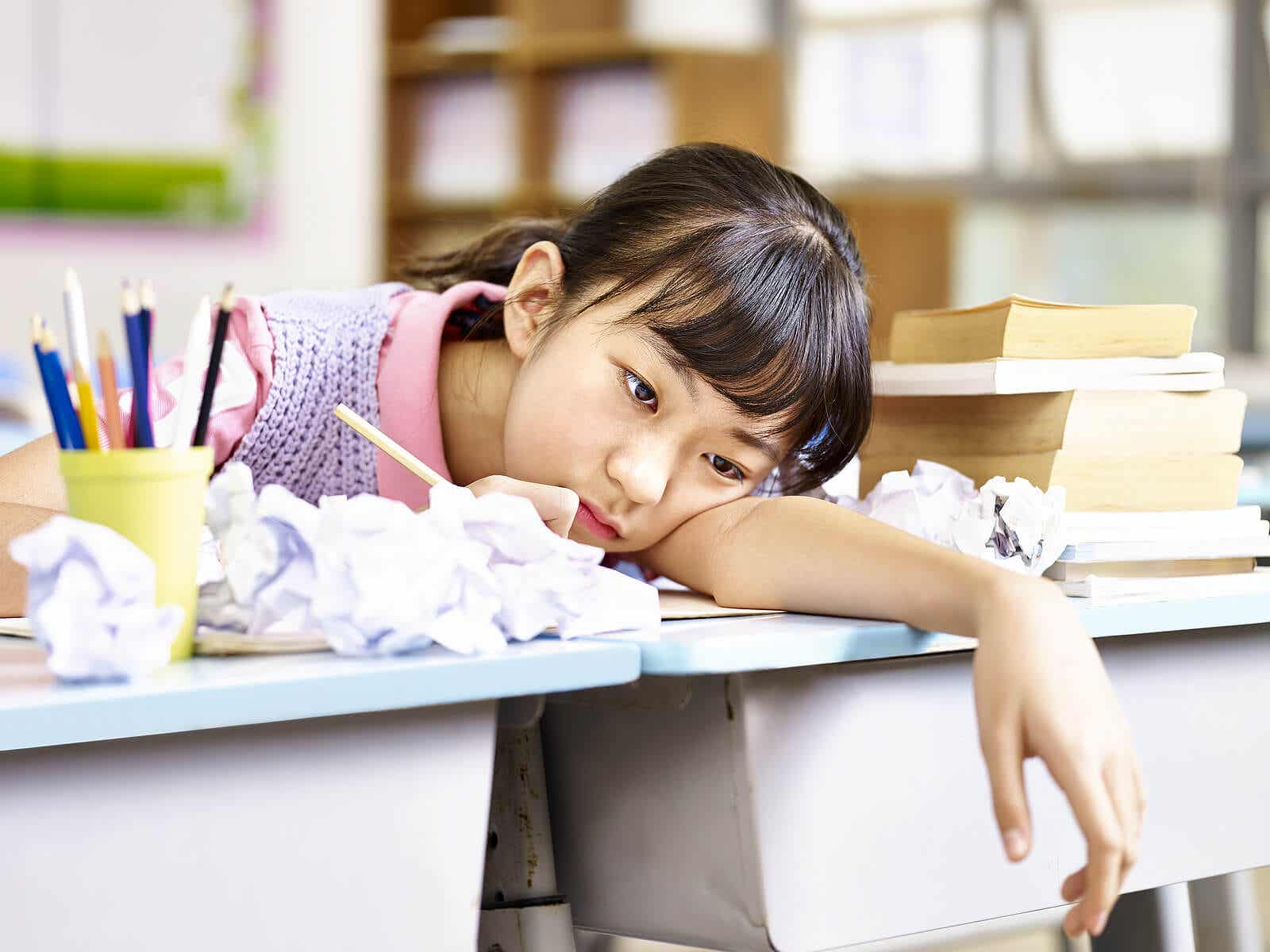 A preteen girl with her head on her school desk surrounded by crumpled up papers, looking bored.