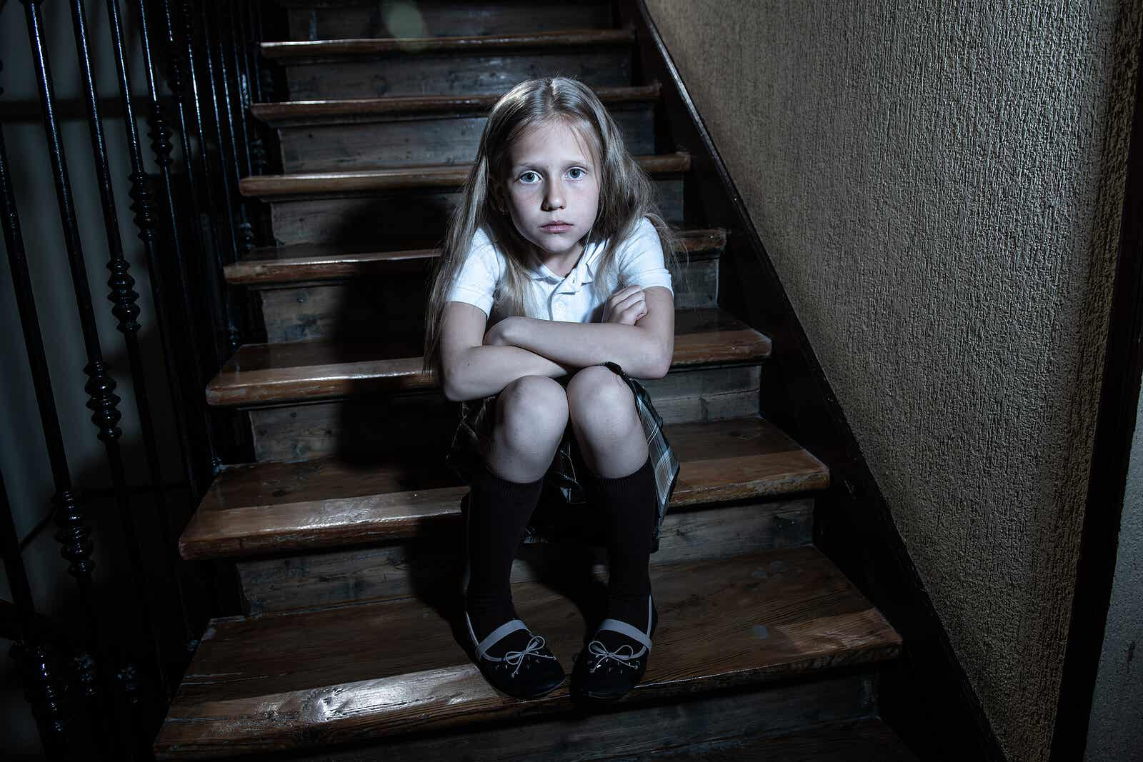 Een kind dat een schooluniform draagt, zit op de trap van haar huis.