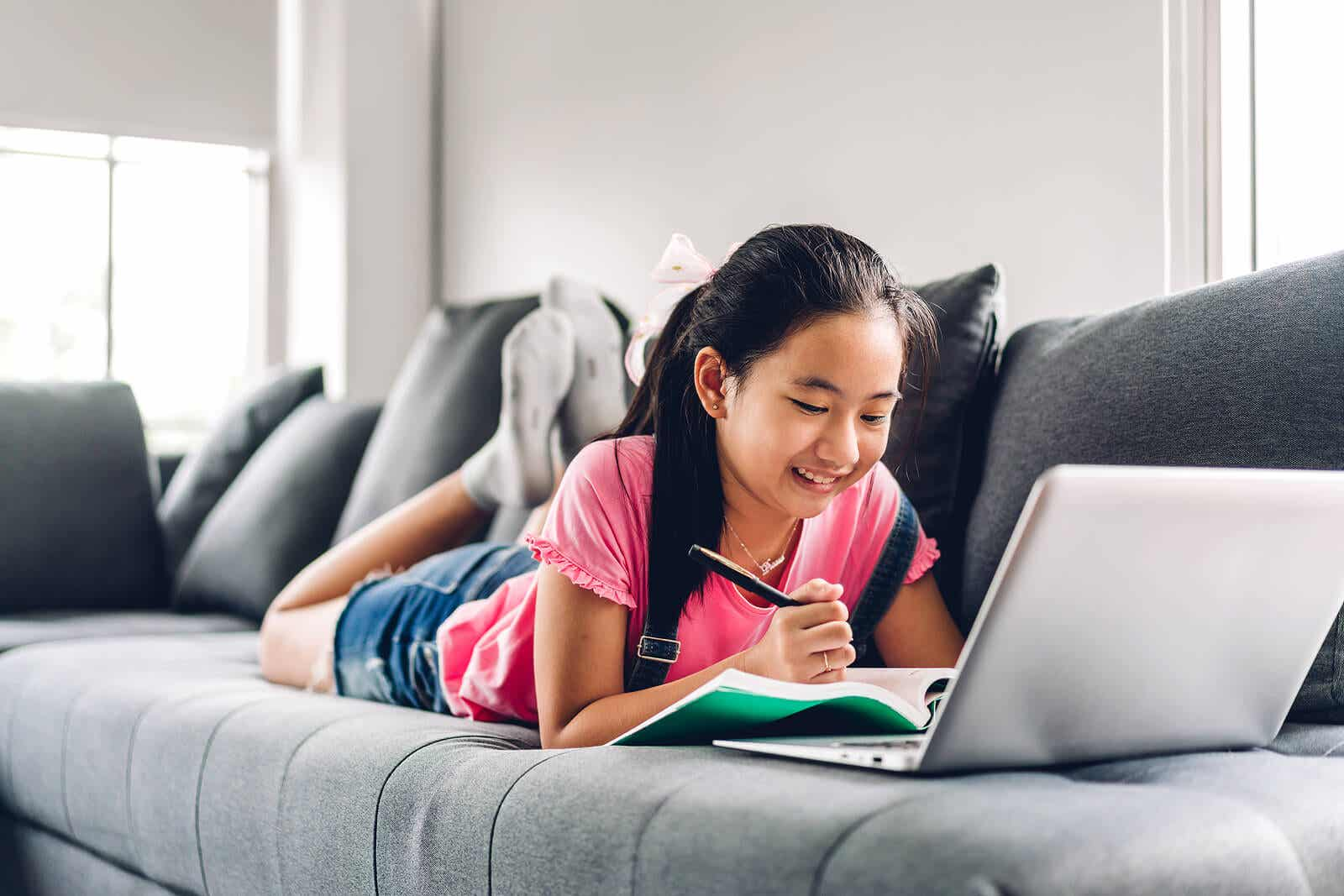 A child lying on a couch doing homework on her laptop computer.