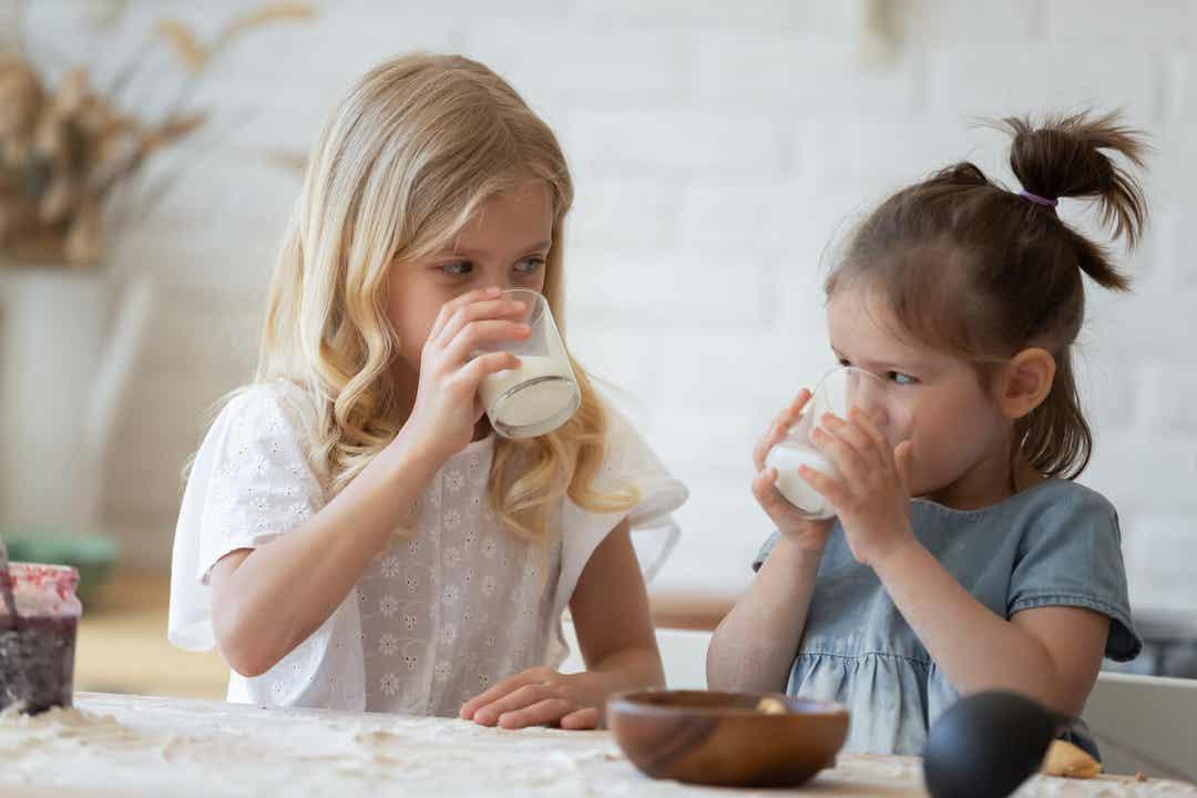Two little girls drinking milk.
