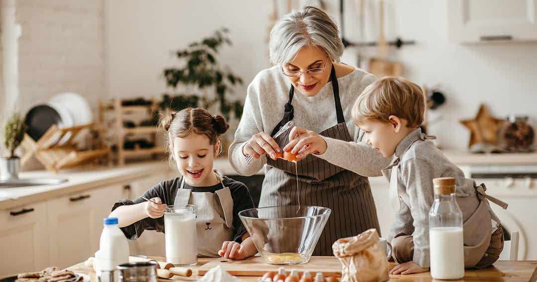 Een grootmoeder die bakt met haar jonge kleinkinderen.