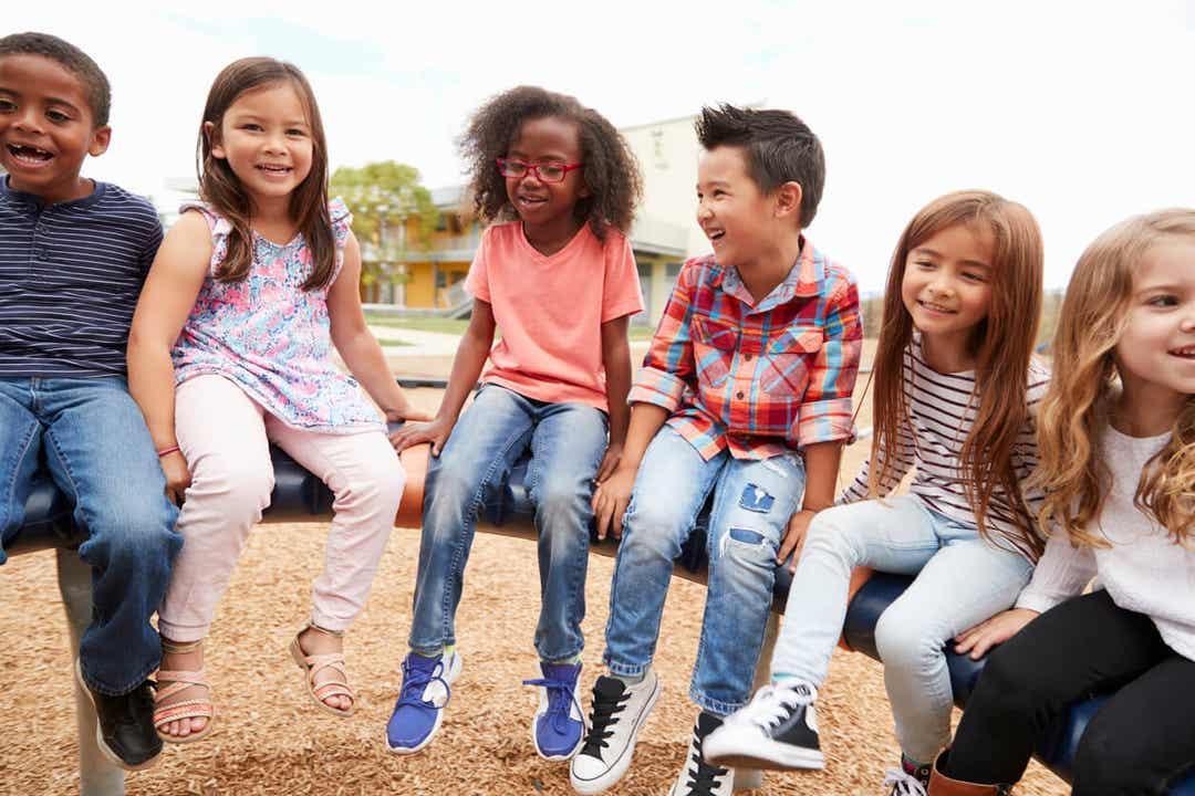 Een diverse groep kinderen die op speeltoestellen zitten.