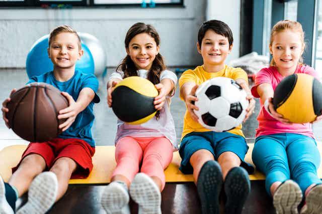 Kinderen houden verschillende ballen vast.