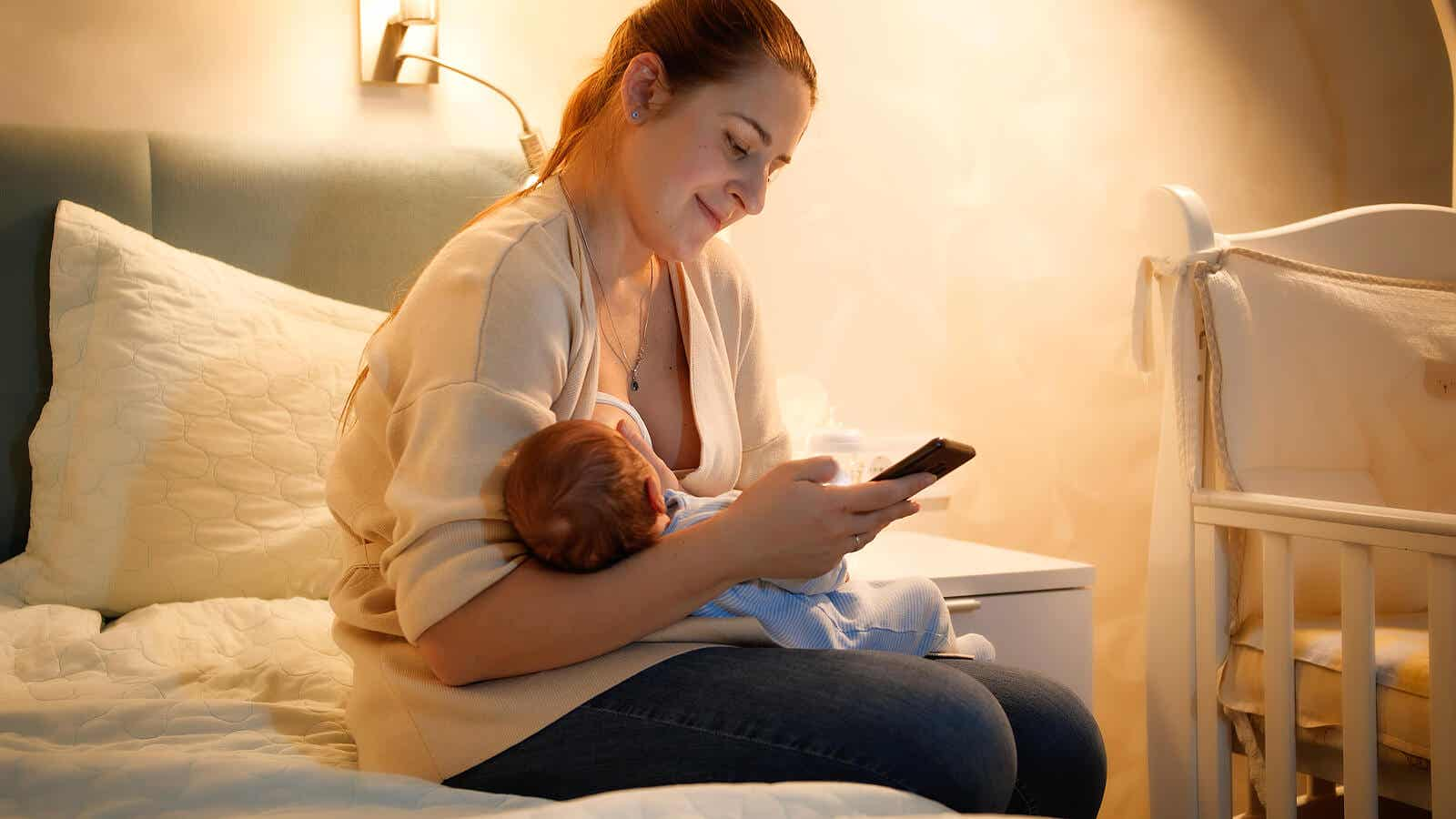 Matka karmiąca noworodka i korzystająca z aplikacji na swoim telefonie.