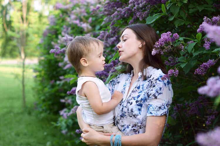 Kobieta trzymająca syna w ramionach w pobliżu krzaka bzu, gdy razem śpiewają.