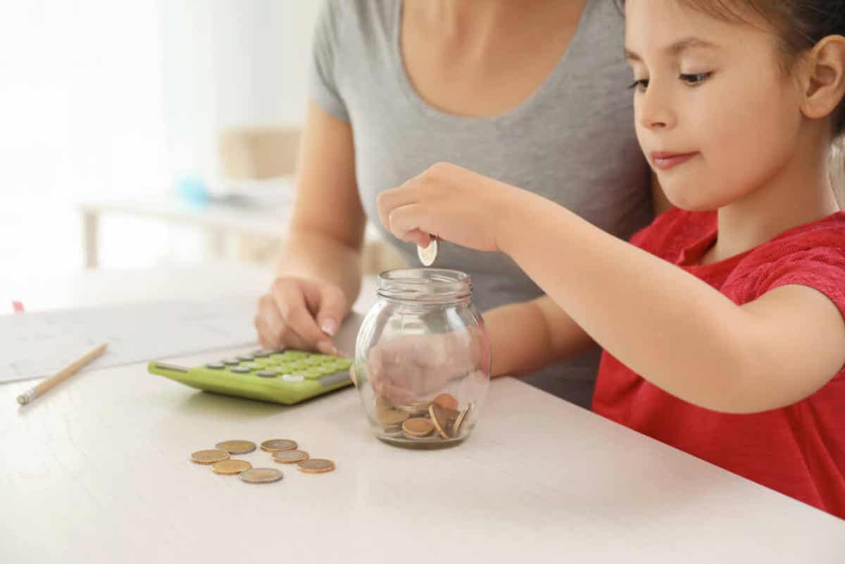 Een moeder gebruikt een rekenmachine terwijl haar jonge dochter kleingeld in een pot laat vallen.