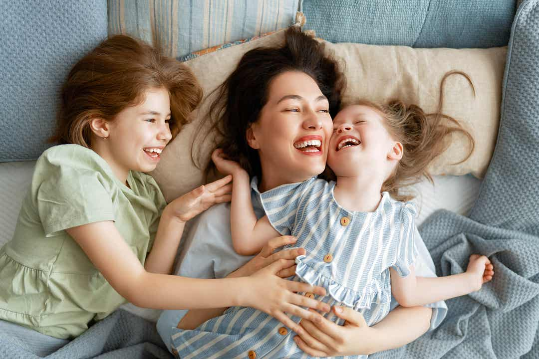 A mother snuggling in bed with her two young daughters.