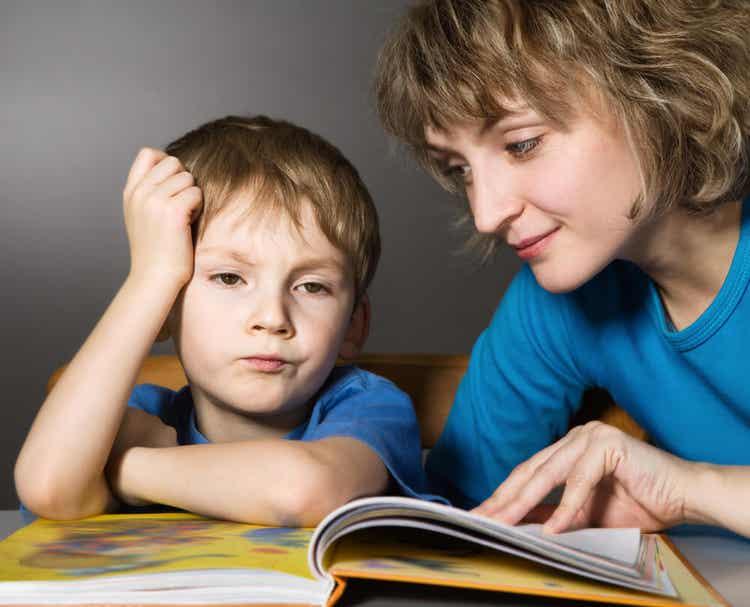 Matka próbująca czytać ze znudzonym dzieckiem.