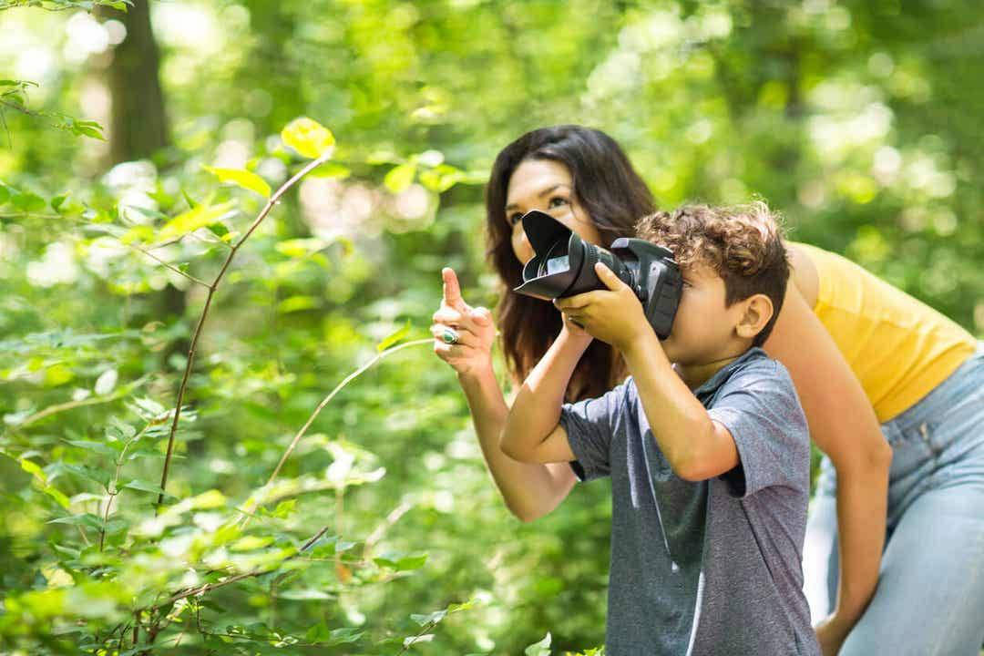 Chłopiec robiący zdjęcia w lesie z mamą.