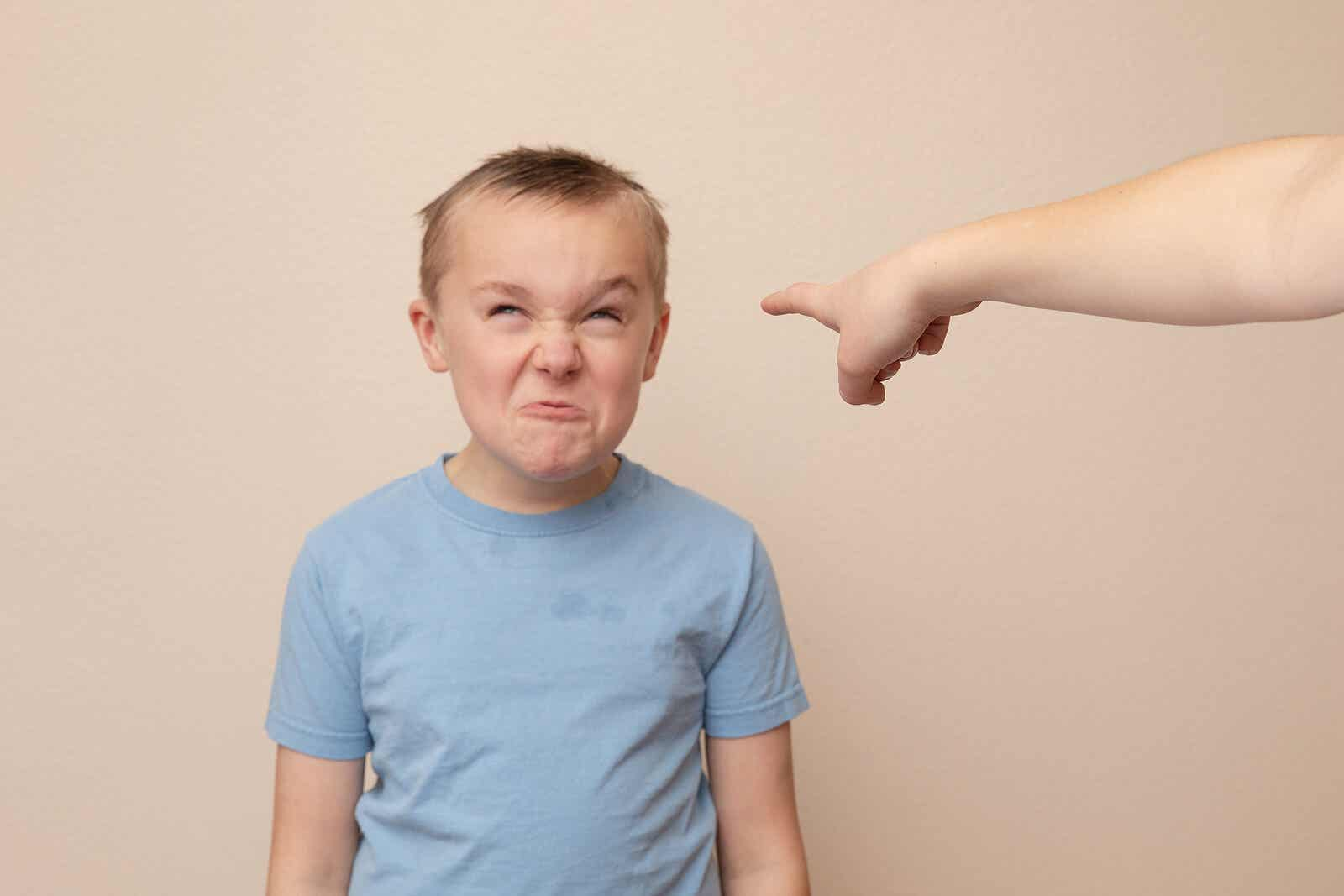 A parent pointing at a child that's making an angry face.