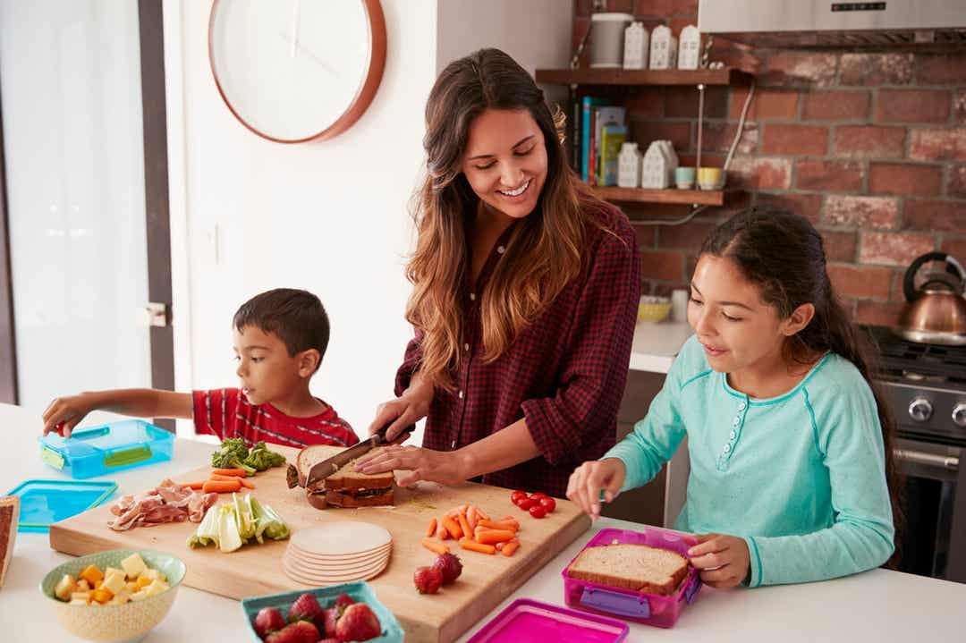 A mother preparing school lunches with her son and daughter.