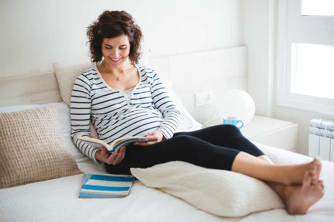 Een zwangere vrouw die in bed een boek met namen leest.