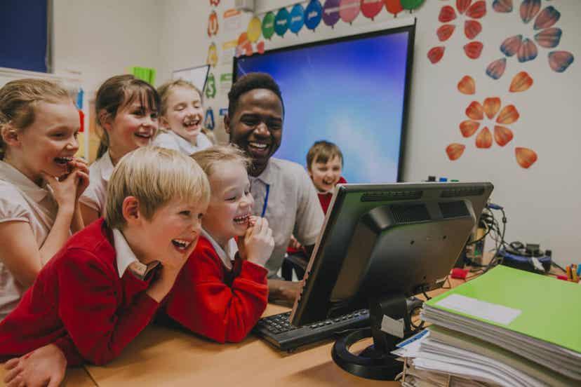 En smilende svart mannlig lærer omgitt av sine barneskoleelever.