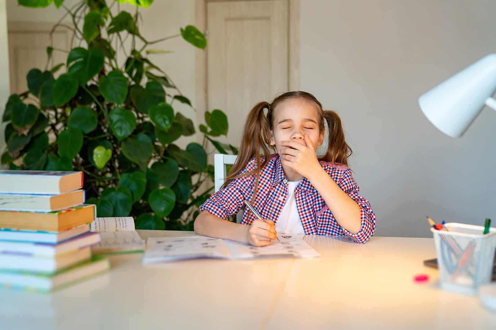 En teenagepige gaber, mens hun laver lektier