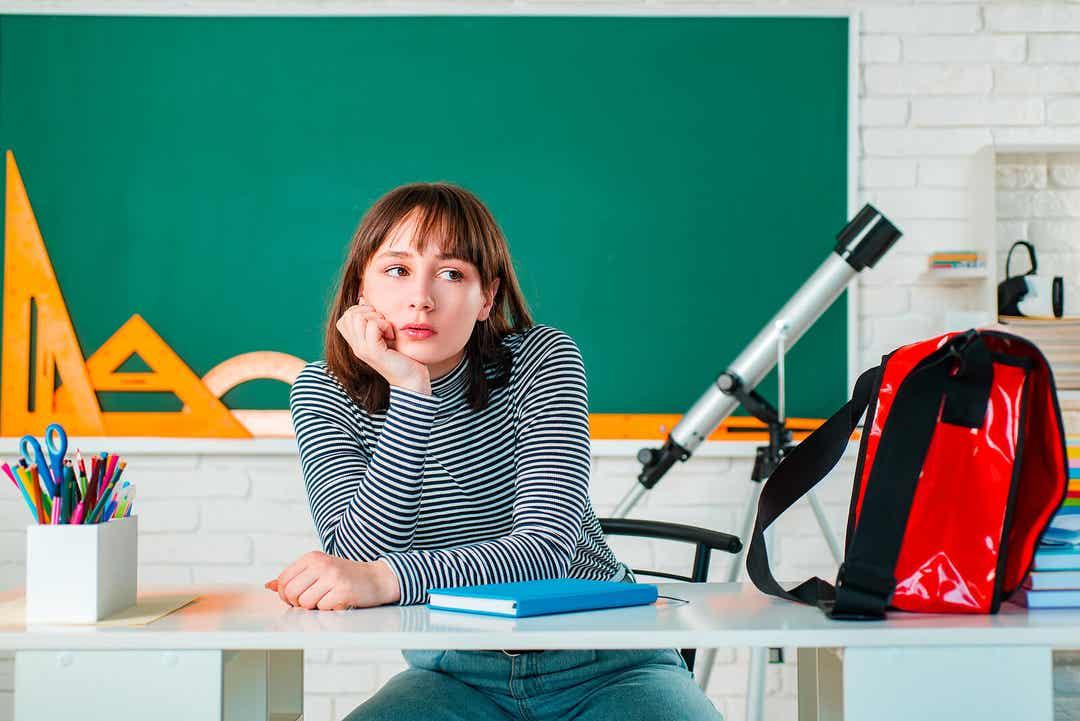 Nastolatka siedzi przy biurku w szkole i wygląda na znudzoną.