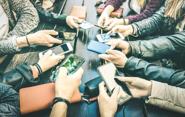 Teenagers sitting on their phones.