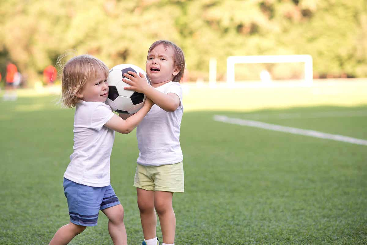 Two kids fighting over a soccer ball.