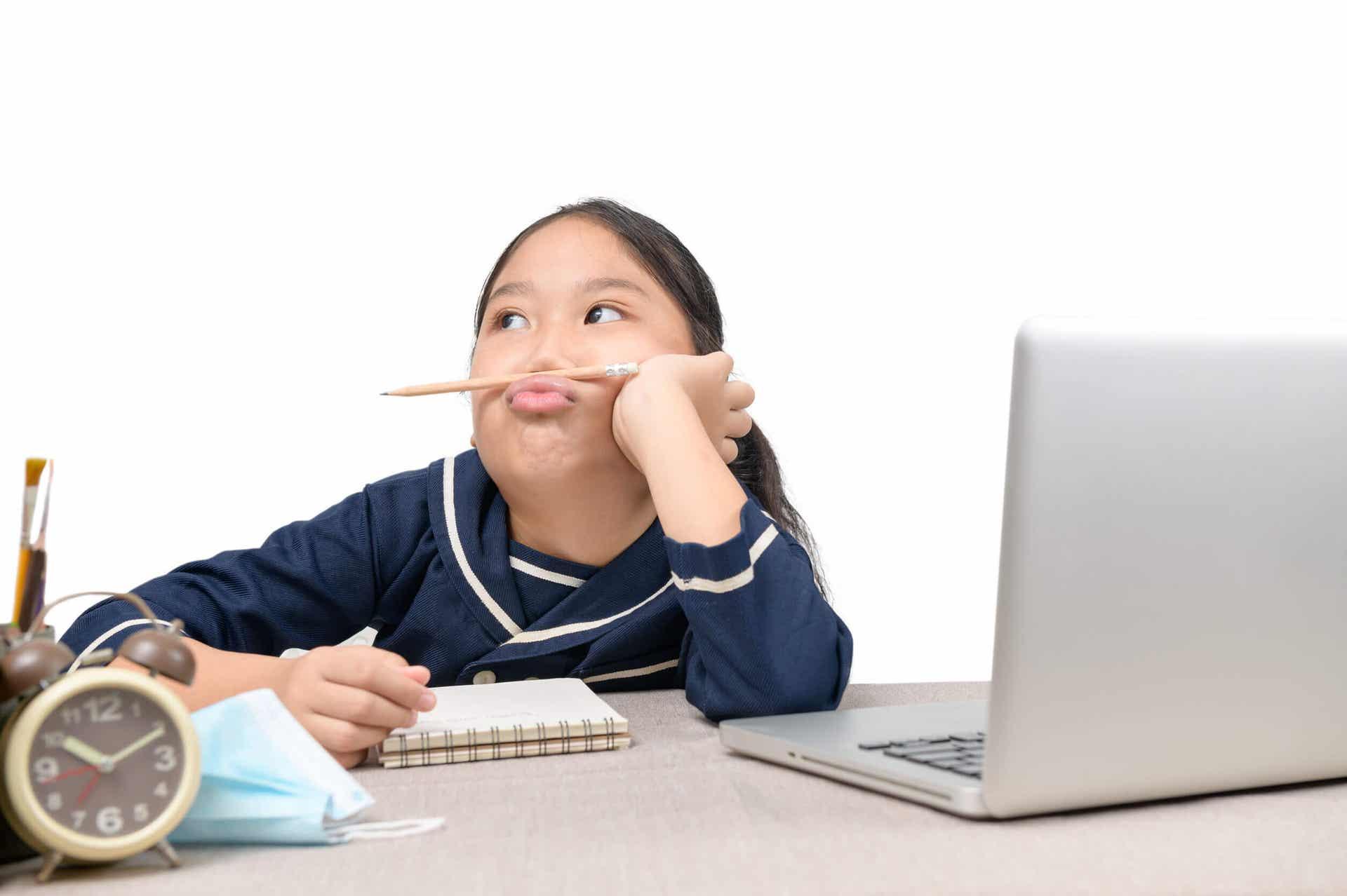 Een meisje zit op een laptopcomputer, kijkt weg en speelt met een potlood.