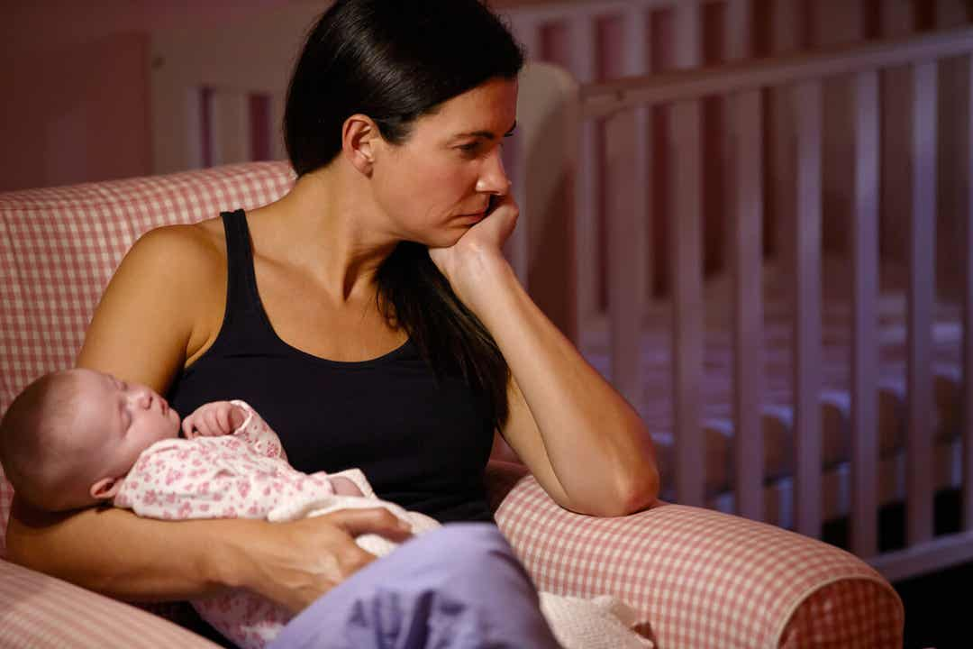 A woman with postpartum depression holding her baby and looking off into the distance sadly.
