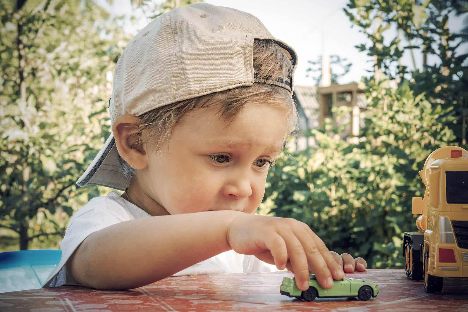 2-year-old boy playing with a toy car.