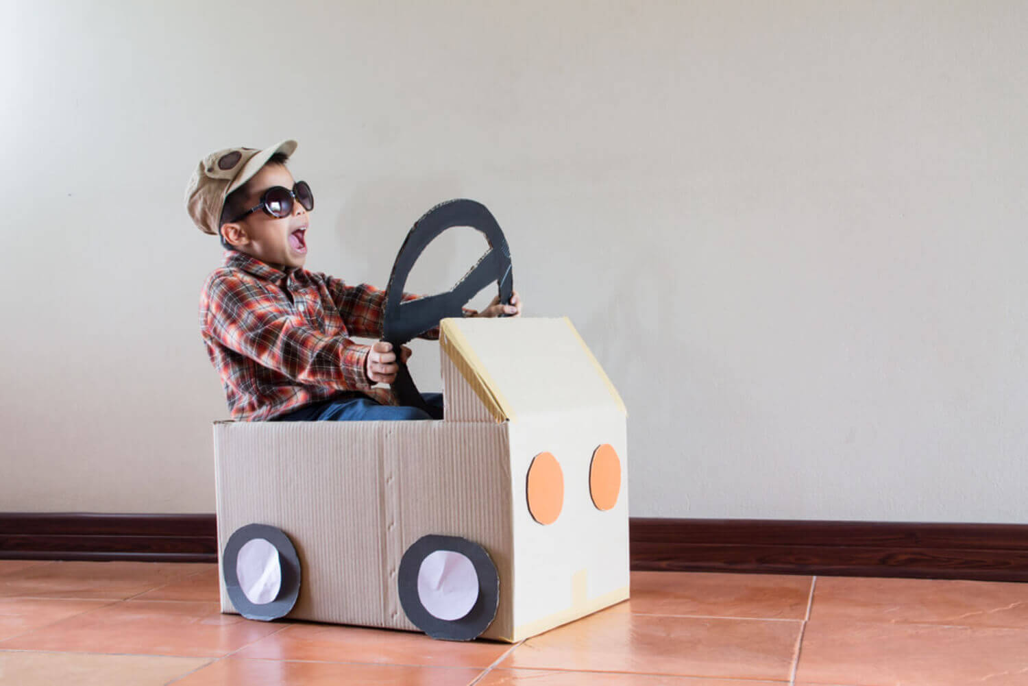 Child playing with a cardboard car, one of the types of play during development.
