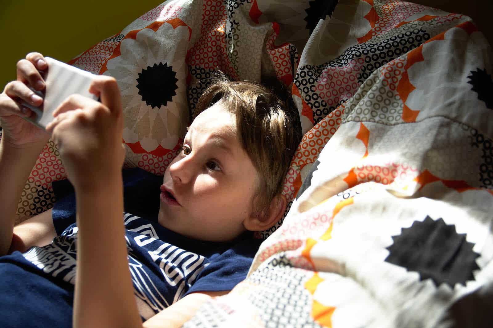 handysüchtig - Junge spielt mit seinem Smartphone