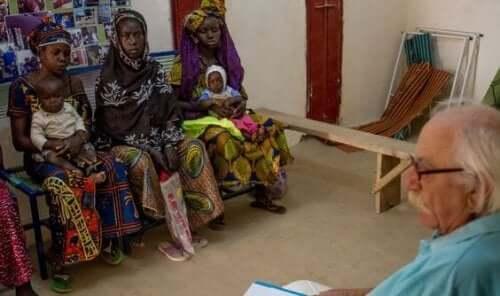 Een dokter in gesprek met een groep moeders in Afrika die het moederschap niet plannen.
