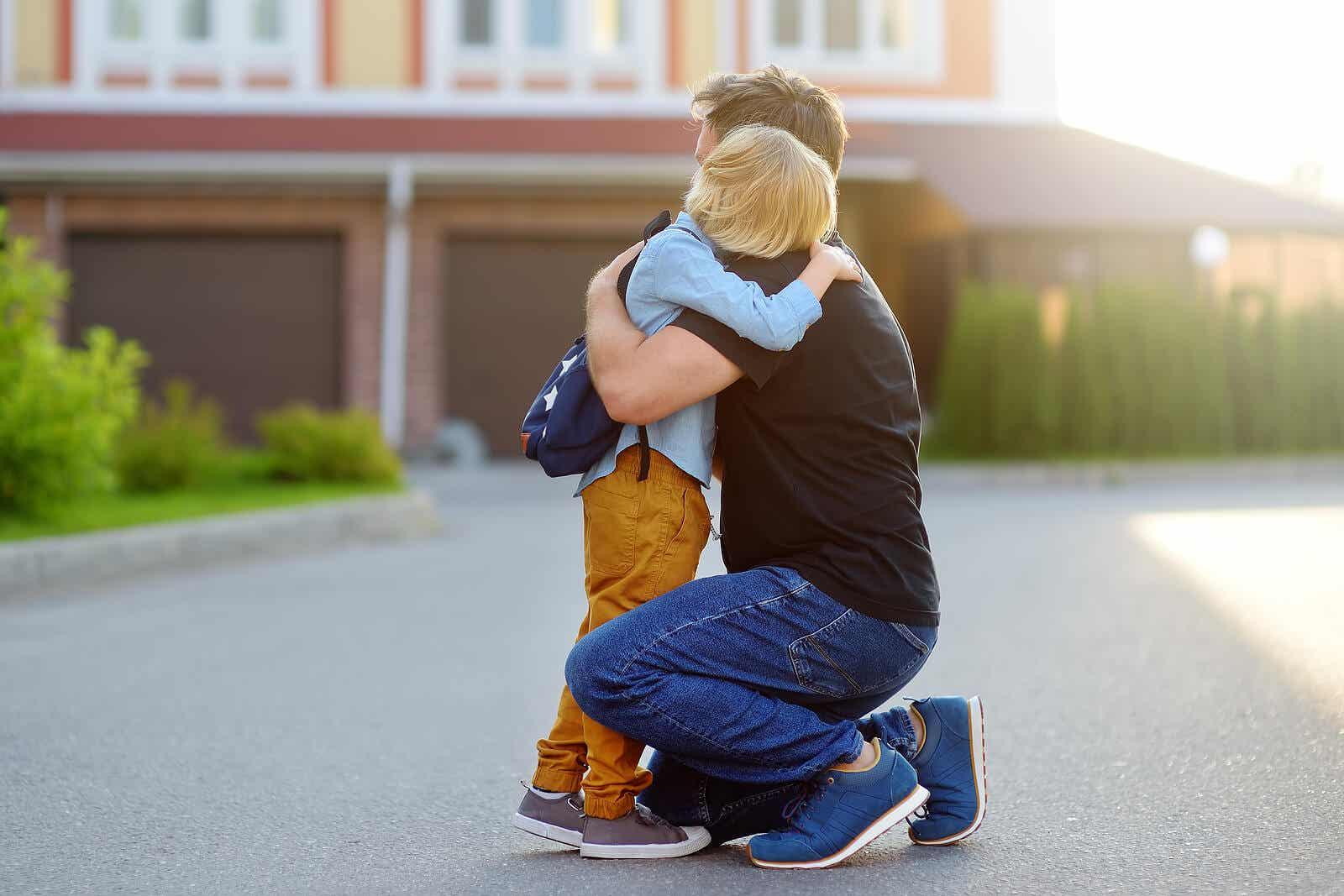 En pojke kramar sin far på väg till skolan.