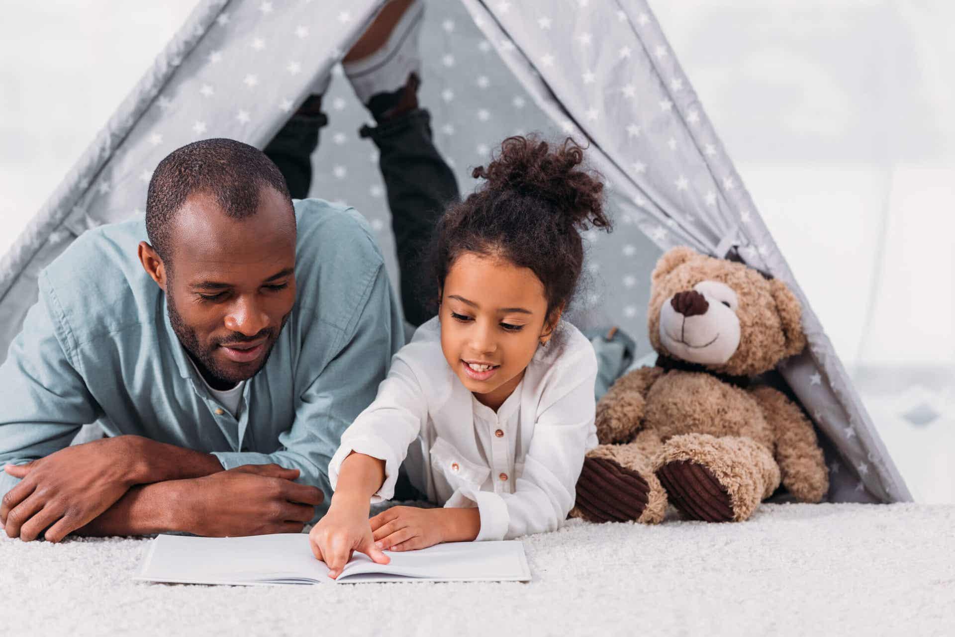 Ojciec i córka leżą na podłodze, czytając książkę.