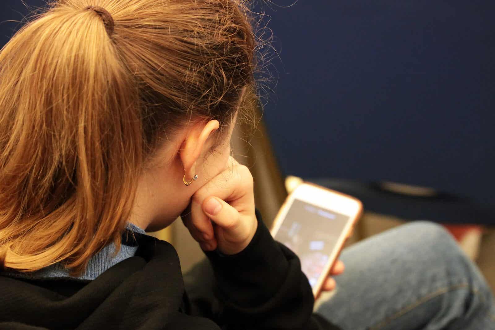 handysüchtig - Teenager checkt sein Mobiltelefon