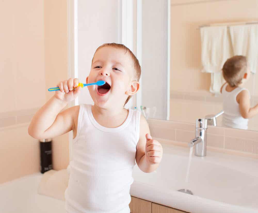 En lille dreng, der børster tænder og smiler