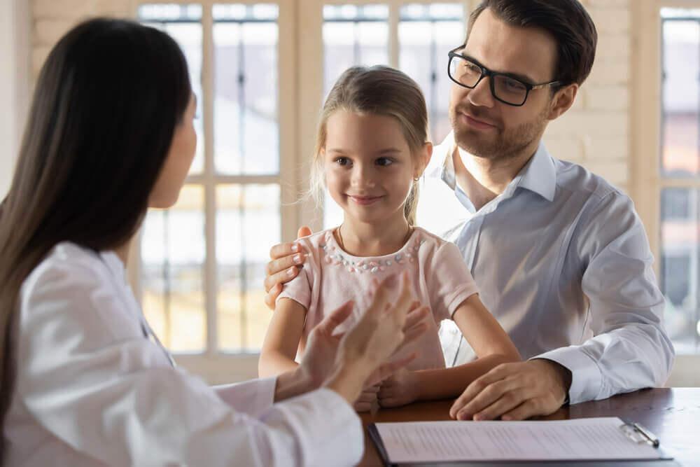 En pappa med sin dotter på barnläkarens kontor.