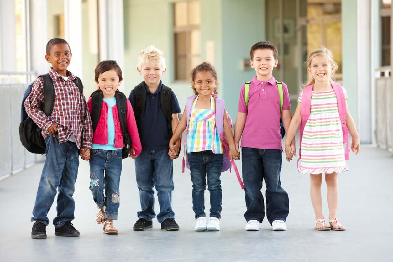 Happy children holding hands in the school hallway.