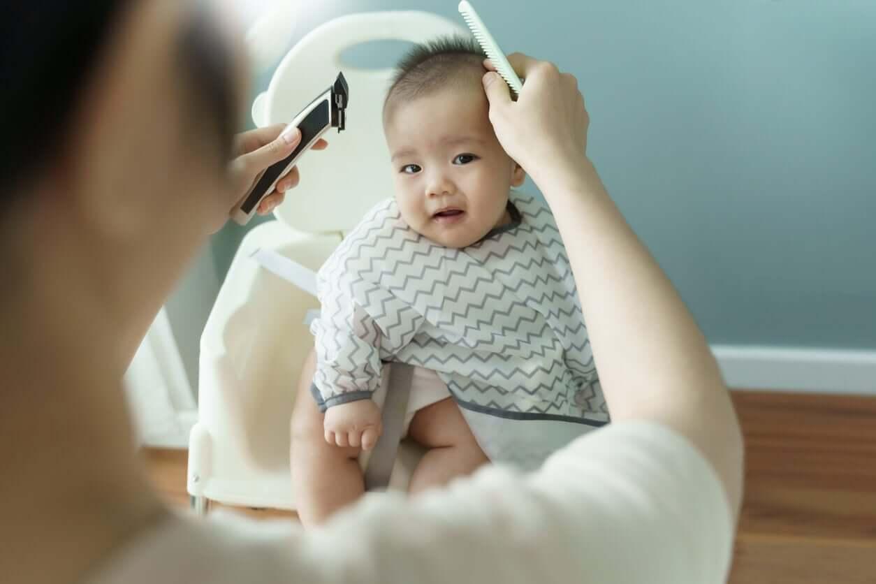 En mor forbereder seg på å klippe babyens hår.