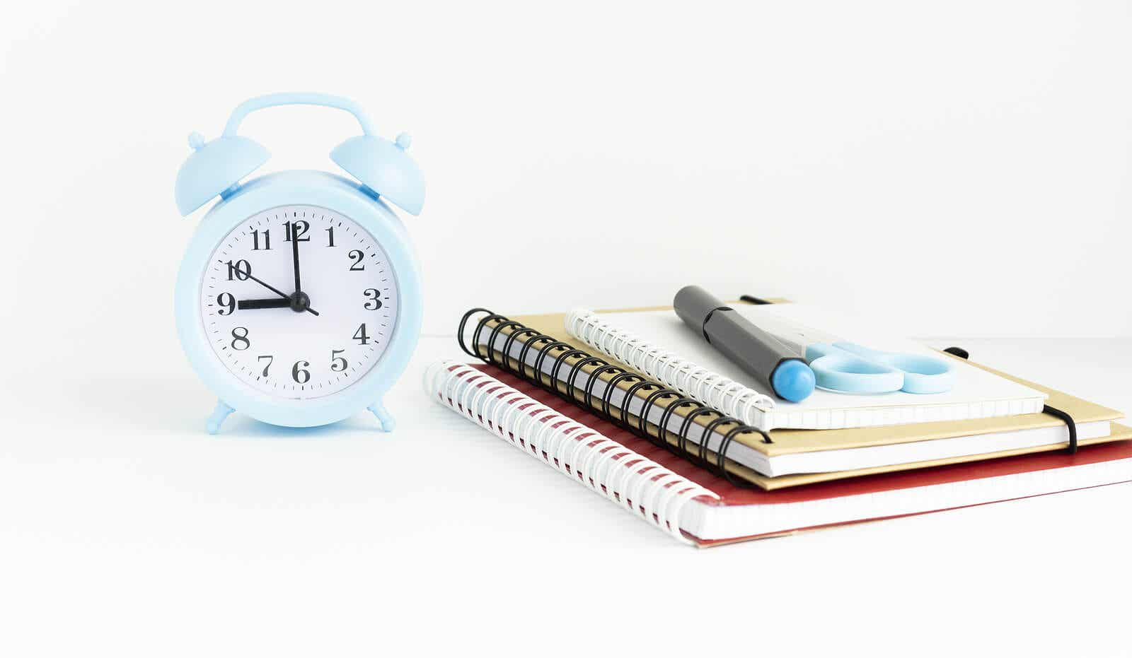 An alarm clock, notebooks, a pen, and scissors.