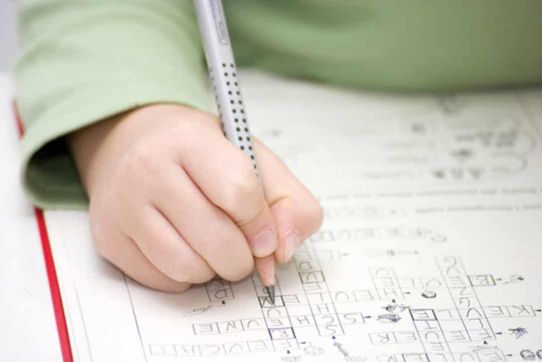 A young child working on a crossword puzzle.